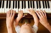 Closeup portrait of a baby learning to play piano with mother - from above poster