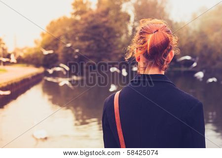 Rear View Of Young Woman Looking At Birds By A River