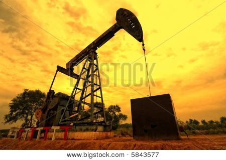 Oil pumping Unit working at sunset time poster