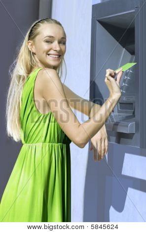 beautiful blond woman near a cash machine with plastic card poster