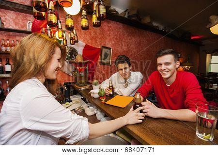 Female bartender serving beer to men at bar counter