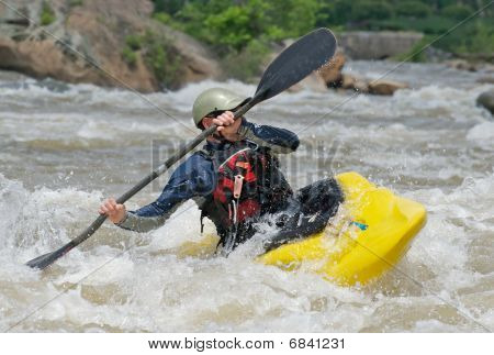 Kayaker fighting river rapids.