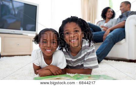 Smiling Siblings Reading Lying On The Floor