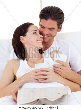 Couple drinking coffee, reading newspaper and lying in the bed poster