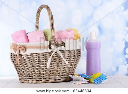 Colorful towels in basket, on table, on bright background