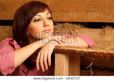 Portrait Of Pensive Girl In Red Shirt, In Village Building. Close-up. Horizontal Format.