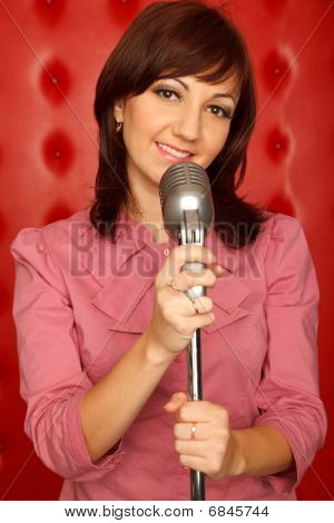 Portrait of girl in red shirt with microphone on rack against red wall. Vertical format.