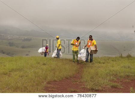 volunteer aid workers carrying toys up a hill to distribute