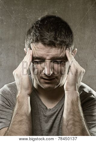 young man suffering migraine and headache in intense pain feeling desperate and sick with hands on tempo isolated on grunge studio background poster
