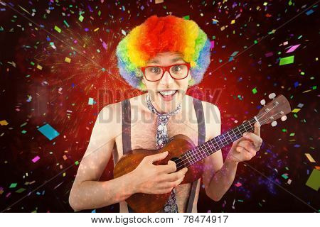 Geeky hipster in afro rainbow wig playing guitar against colourful fireworks exploding on black background