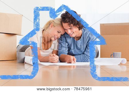 Happy couple organizing their new home against house outline