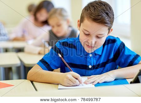 education, elementary school, learning and people concept - group of school kids with pens and notebooks writing test in classroom