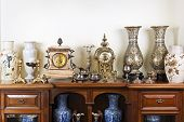 Various antique clocks vases and candlesticks on display poster