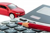 a car and a red pen lying on a calculator. cost of gasoline, wear and insurance. car costs are not paid by commuter tax. poster