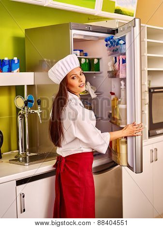 Female chef wearing uniform at cafeteria. Girl opens fridge.