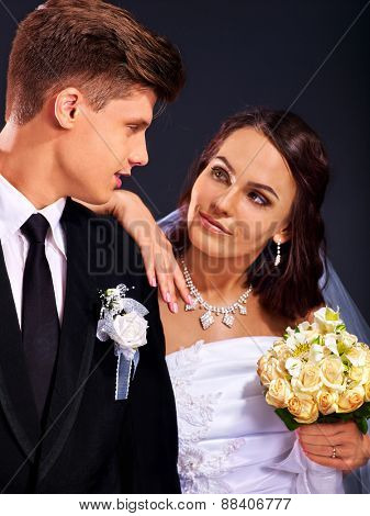 Bride and groom wearing wedding dress and costume fn black background.