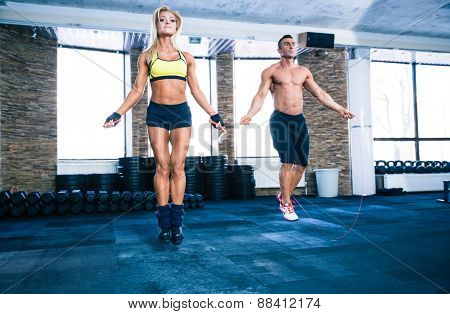 Handsome muscular man and beautiful sporty woman workout with jumping rope in gym
