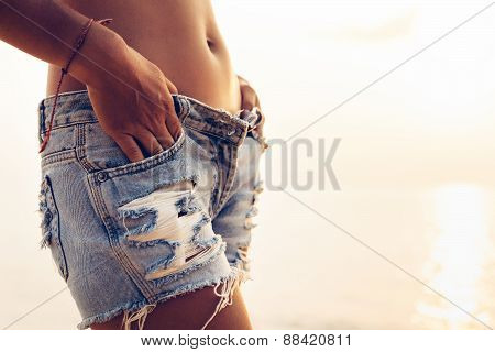 Woman In Jeans Shorts Posing On The Beach