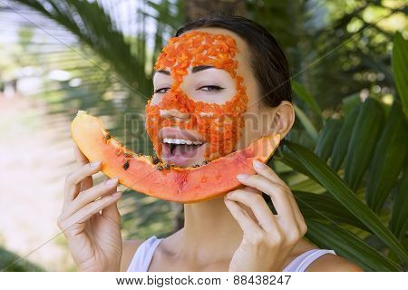 Beautiful caucasian woman having fresh fruit papaya natural facial mask apply antioxidant skin care and wellness. Facial vitamin mask of papaya slices at spa salon (outdoors). Healthy exotic food poster
