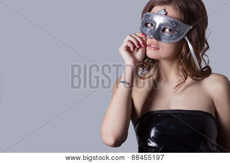 beautiful sexy girl with full lips in black leather dress wore a gray mask , festive image