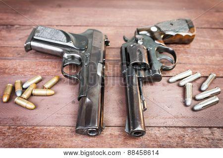 Black Revolver Gun And Semi-automatic 9Mm Gun On Wooden Background