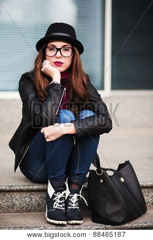 The Stylish City Girl In Sunglasses  Sits On Steps