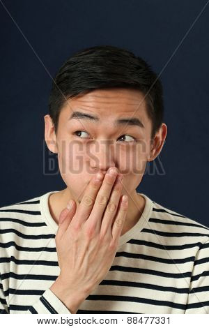 Funny young Asian man covering his mouth by palm and looking sideways