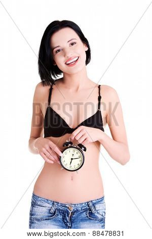 Young topless woman with alarmclock.