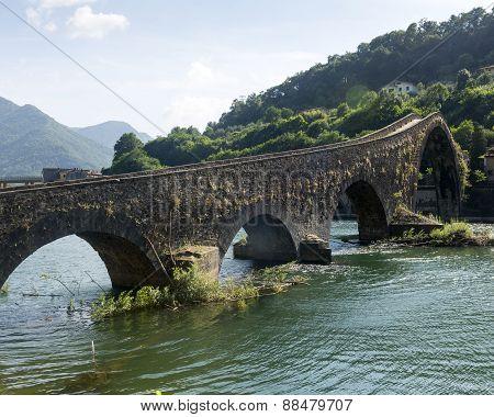 """Ponte della Maddalena aldo wnown as """"Ponte del DIavolo (Evil's Bridge) near Borgo a Mozzano (Lucca Tuscany Italy) over the Serchio river at summer poster"""