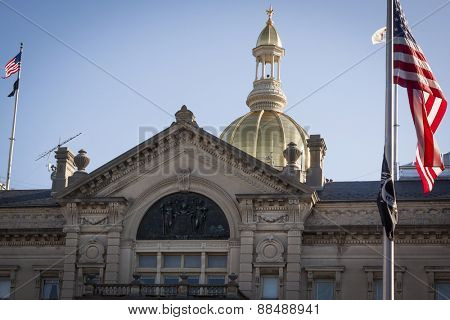 TRENTON, NJ - APRIL 4, 2015: The American Flag flying in front of the New Jersey State House located in Trenton. The capitol building for the state of New Jersey is located on State St.