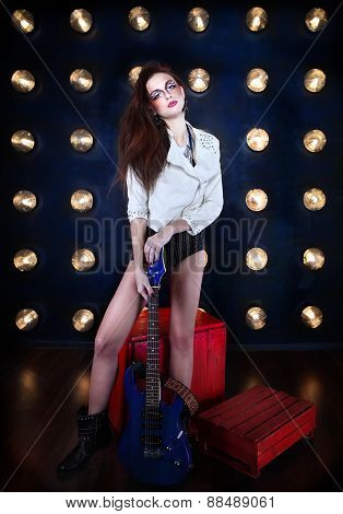 Attractive Girl With Cool Make Up Holding Guitar