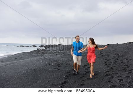 Couple walking during travel holidays on secluded black sand beach. Full length shot of people in love running together having fun during summer travel vacation on Big Island, Hawaii, USA.