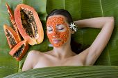 Beautiful caucasian woman having fresh papaya natural facial mask apply skin care and wellness. Fresh papaya fruit. Facial mask of papaya slices at spa salon poster