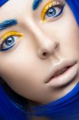 Beautiful girl in a bright blue wig in the style of cosplay and creative makeup. Beauty face. Art image. Picture taken in the studio on a yellow background. poster