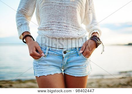 Close-up of young woman in white pullover and denim shorts