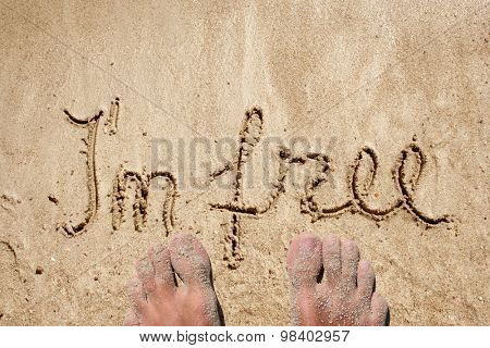 I`m free hand written in sand on a beach on an exotic island background with feet