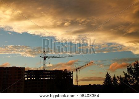 Industrial Tower Crane On A Construction Site And Building Silhouettes At Sunset Sky