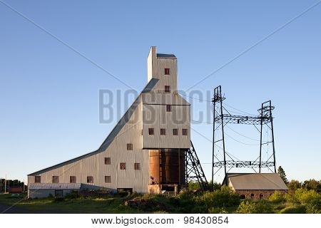 Abandoned shaft house and other industrial structures from an abandoned copper mine. Now part of a Historic National Park in Upper Michigan. Warm evening light with copy space in upper half of frame. poster