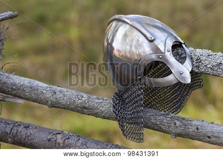 Steel Viking Knight helmet hangs on an old traditional wooden fence. Fuzzy background. Retro. poster