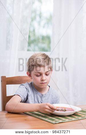 Unhappy Boy Eating Soup