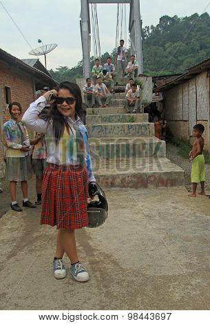 Schoolgirl is setting the sunglasses straight in small village Bukit Lawang, Indonesia