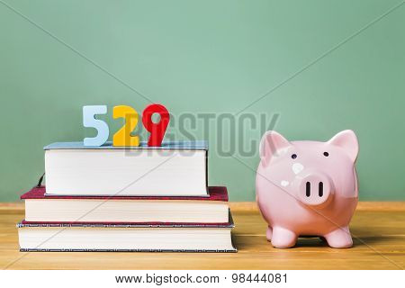 529 College Savings Plan Theme With Textbooks And Piggy Bank