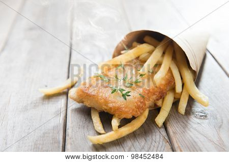 Fish and chips. Fried fish fillet with french fries wrapped by paper cone, on wooden background.