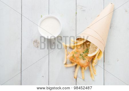 Fish and chips. Above view fried fish fillet with french fries wrapped by paper cone, on bright wooden background.