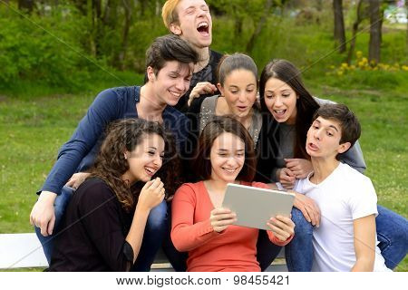 Group of young adults browsing a tablet outside and goofing around