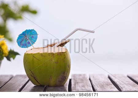 Coconut Water Drink Served In Coconut With Drinking Straw On The Beach