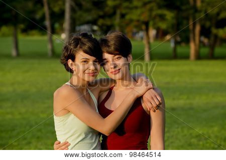 Two short hair girlfriends hugging outside in a park.