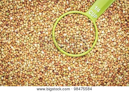 background and texture of buckwheat kasha with a measuring scoop - gluten free grain