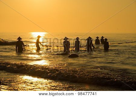 Fishermen draw up a net to catch fishes on the beach
