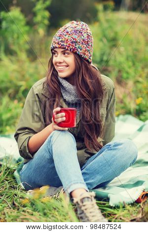 adventure, travel, tourism, hike and people concept - smiling young woman with cup sitting in camping poster